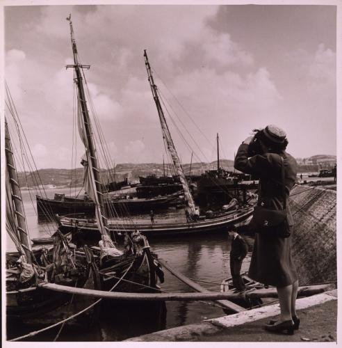 American tourist, Gertrude LeGendre, photographing boats in Lisbon, Portugal.